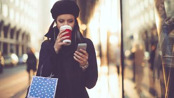 Female adult reading her mobile phone and drinking a coffee whilst walking and holding a shopping bag.