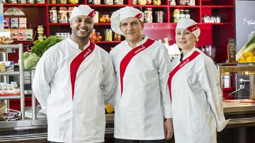 A group of Sodexo chefs posing for a picture in front of a counter.